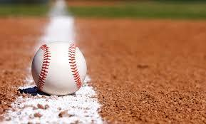 A close-up image of a baseball laying on a baseball field.